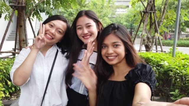 vídeos de stock e filmes b-roll de three friends taking a selfie together in the city - povo tailandês