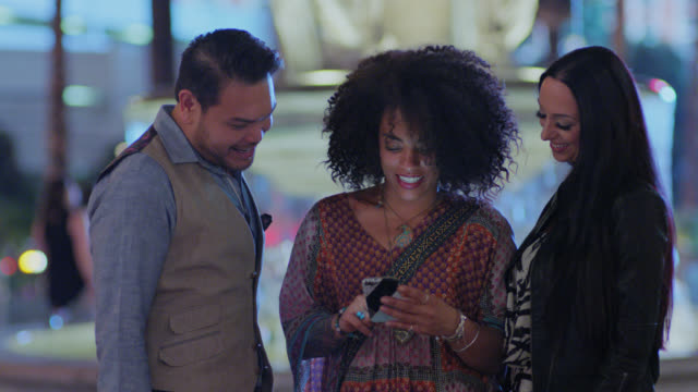 SLO MO. Three friends talk and laugh while looking at smartphone by fountain on Las Vegas strip at night.