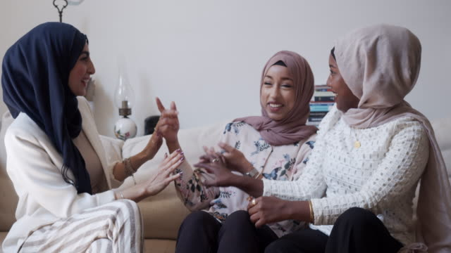 three friends talking together sitting on the sofa at home - hijab stock videos & royalty-free footage