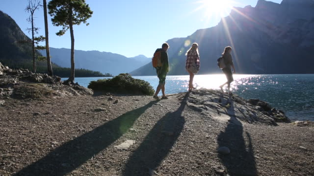 Three friends walk along mountain lake edge towards sunrise
