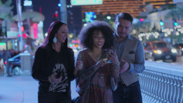 Three friends walking Las Vegas strip at night follow directions on smartphone and laugh.