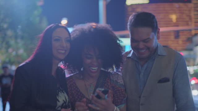 three friends walking las vegas strip at night look at smartphone and laugh. - nightlife stock videos & royalty-free footage