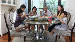 Three Generation Asian Family Serving and Eating Lunch at Home