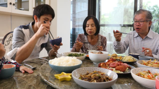 three generation asian family serving and eating lunch at home - asian stock videos & royalty-free footage