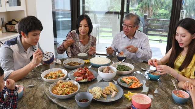 three generation asian family serving and eating lunch at home - chinese ethnicity stock videos & royalty-free footage