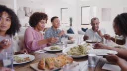 Three generation black family sitting at dinner table serving spaghetti, panning shot