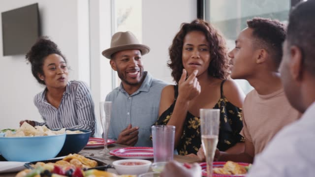 Drei schwarze Familie sitzen zusammen am Esstisch und sprechen während einer Familienfeier