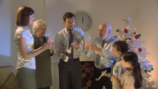 Three generation family count down to midnight on new year, man opens bottle of champagne