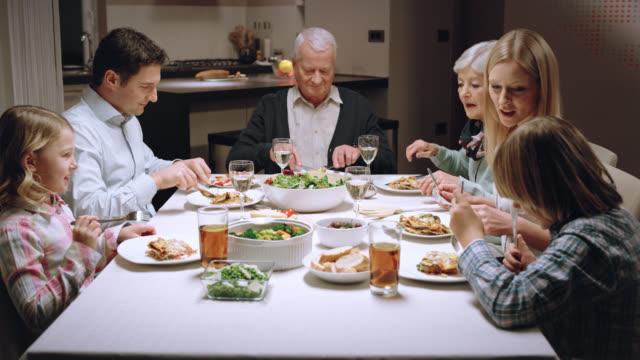 vidéos et rushes de trois génération famille manger le dîner - déjeuner