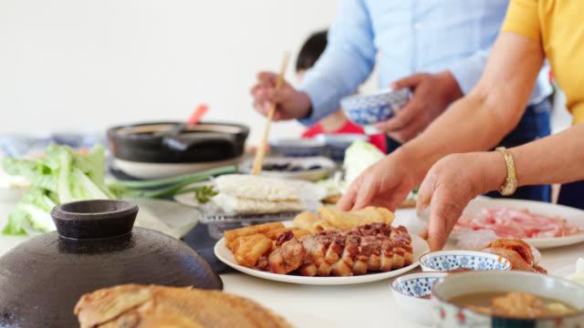 vídeos de stock, filmes e b-roll de família de três gerações que prepara o jantar chinês dos anos novos junto - ano novo chinês