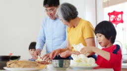 Three generation family preparing Chinese New Years dinner together