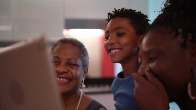 vidéos et rushes de famille de trois générations regardant le film sur la tablette numérique - vie réelle