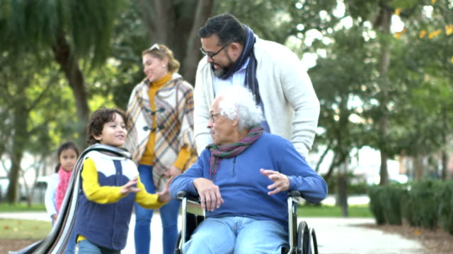 three generation hispanic family taking walk - persons with disabilities stock videos & royalty-free footage
