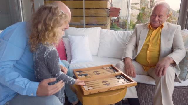 自宅でバックギャモンを演奏する3世代 - 余暇 ゲームナイト点の映像素材/bロール