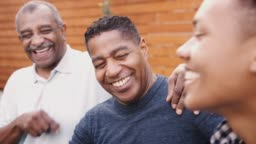Three generations of black family men laughing together outdoors, close up
