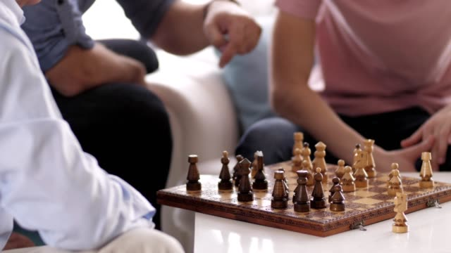 Three generations of men playing chess at home