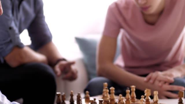 stockvideo's en b-roll-footage met drie generaties van mannen spelen schaken thuis - spelletjesavond