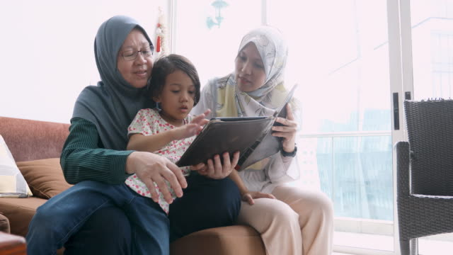 three generations of muslim women reading together - malay family stock videos and b-roll footage