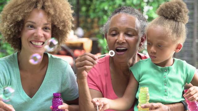 vídeos y material grabado en eventos de stock de three generations of women blowing bubbles - nieta