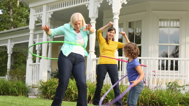 ms three generations of women hula hooping in front of house / richmond, virginia, usa - enkelin stock-videos und b-roll-filmmaterial