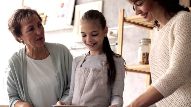 three generations of women serving cookies - granddaughter stock videos & royalty-free footage