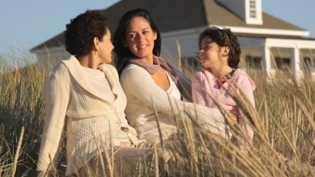 ms pan three generations of women sitting together on beach dunes / eastville, virginia, usa - virginia beach stock videos & royalty-free footage