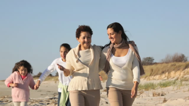 ws ts three generations of women walking together on beach / eastville, virginia, usa - arm around stock videos & royalty-free footage