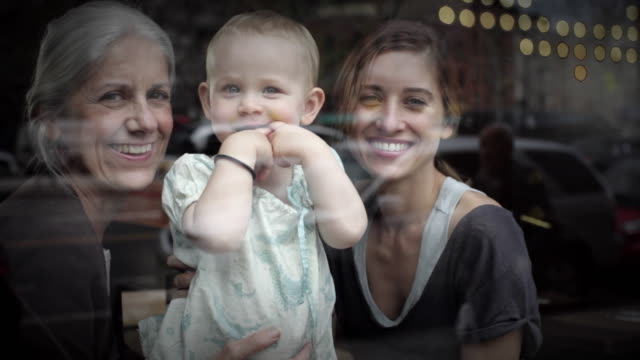 ms three generations together in window of café looking out at street / new york city, new york, usa - enkelin stock-videos und b-roll-filmmaterial