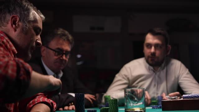 drei herren spielen poker im casino in der nacht - poker stock-videos und b-roll-filmmaterial