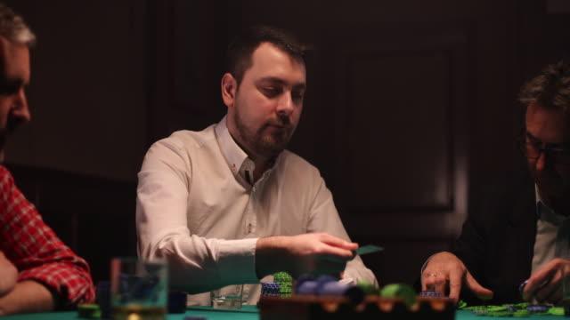 vidéos et rushes de trois messieurs jouant au poker dans la chambre noire - poker