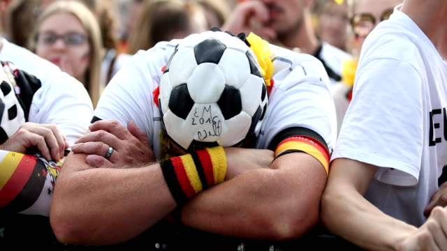three german fans with caps, looking like a football, are seriously disappointed and cannot believe that germany is loosing the 2018 fifa world cup... - fußballweltmeisterschaft stock-videos und b-roll-filmmaterial