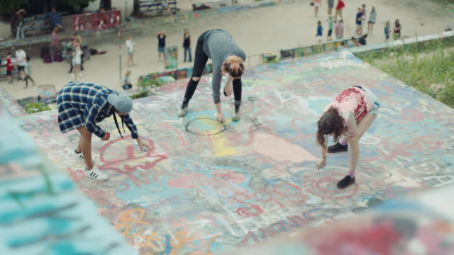 three girl friends make designs with spray paint on graffiti wall in urban park. - malen stock-videos und b-roll-filmmaterial