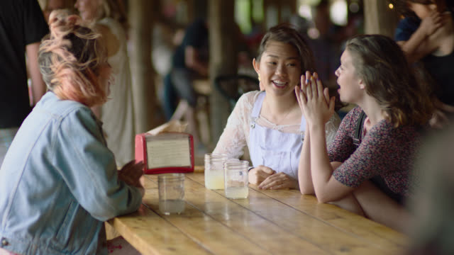 ws. three girl friends talk gossip and bang on picnic table while waiting for food at austin restaurant. - bib overalls stock videos and b-roll footage
