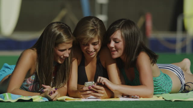 three girls at a water park looking at a cell phone
