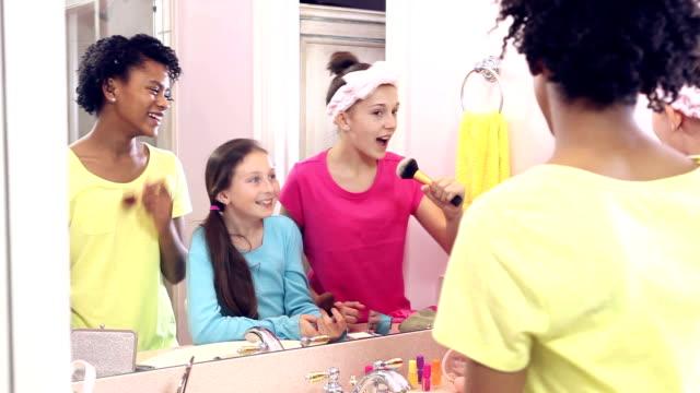 Three girls at sleepover putting on makeup