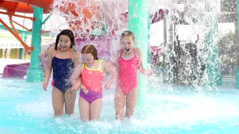 stockvideo's en b-roll-footage met drie meisjes op waterpark lopen onder de fontein - swimwear