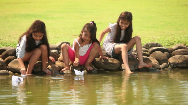 Three girls floating paper boat on the water