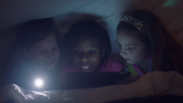 three girls huddle under the covers with a flashlight and interact with digital tablet at fun sleepover party. - decor stock videos & royalty-free footage