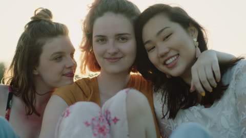 ms slo mo. three girls hug and smile at camera in open field at magic hour. - menschengruppe stock-videos und b-roll-filmmaterial