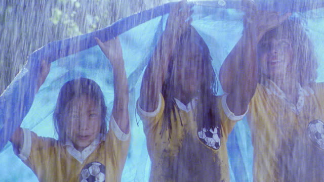MS three girls in muddy soccer uniforms standing under tarp in heavy rain