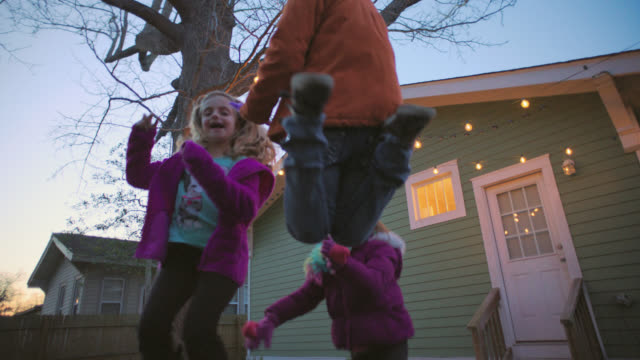 MS SLO MO. Three girls jump on backyard trampoline in slow motion and smile at camera.