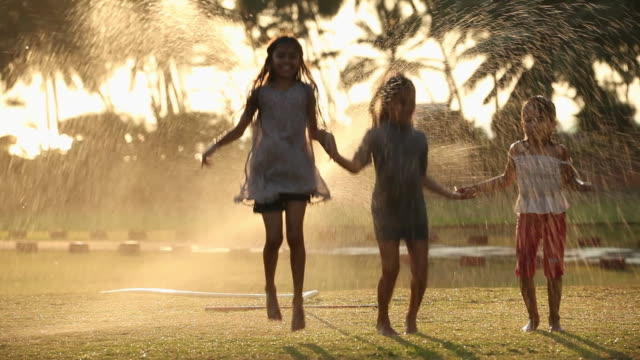 Three girls jumping in front of a lawn sprinkler in a park