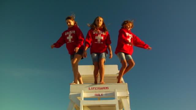 slo mo, ms, la, three girls (10-11, 12-13) jumping off lifeguard chair, provincetown, massachusetts, usa - 12 13 år bildbanksvideor och videomaterial från bakom kulisserna