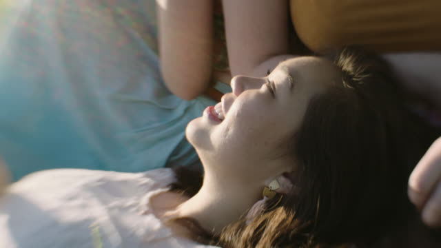 MS SLO MO. Three girls laugh and smile at each other in field of flowers.