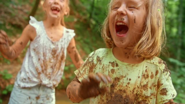 slo mo three girls laughing while playing in a forest creek covered in mud from head to toe - mud stock videos & royalty-free footage