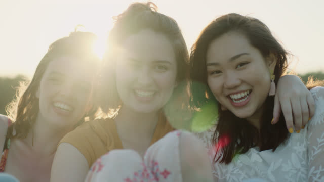 MS SLO MO. Three girls lean on each each other and smile at camera in open field at sunset.