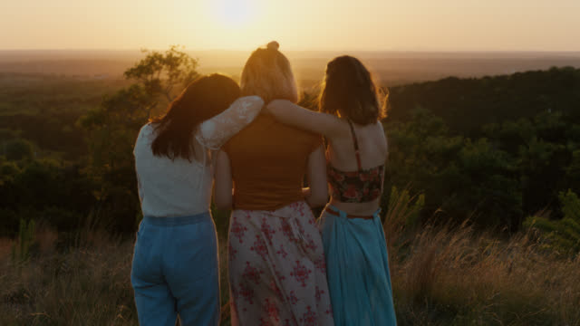 ws slo mo. three girls lean on each other and watch sunset from mountainside field. - arm around stock videos and b-roll footage