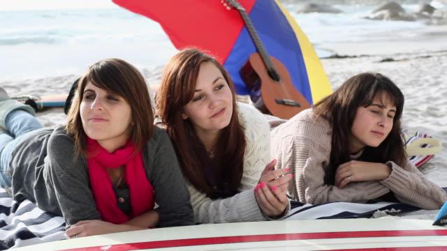 vídeos de stock, filmes e b-roll de three girls lying on the beach - toalha de praia
