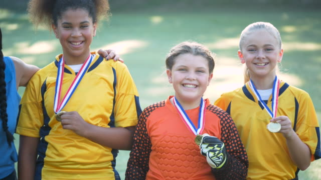 three girls on soccer team show off their medals - award stock videos & royalty-free footage