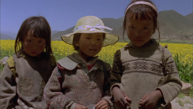 three girls, one wearing straw hat, stand in front of yellow field and mountains looking at camera, bhutan available in hd. - straw hat stock videos & royalty-free footage